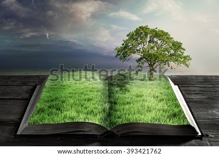 open book with green grass and big tree - stock photo