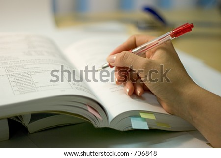 open book with hand and red pen, soft focus - stock photo