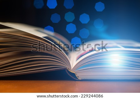 Open book with light inside - stock photo