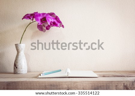 Open book with pencil and Flowers, home decoration concept. - stock photo