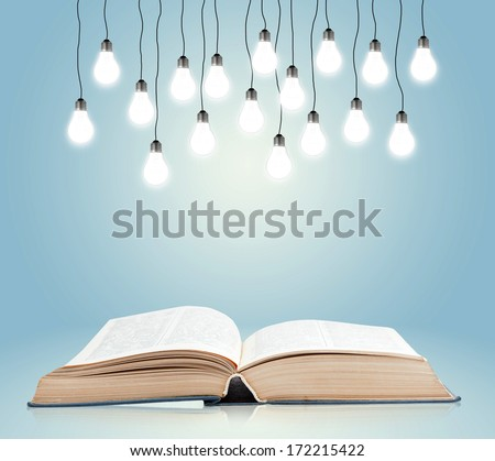 Open book with shining lamps - stock photo