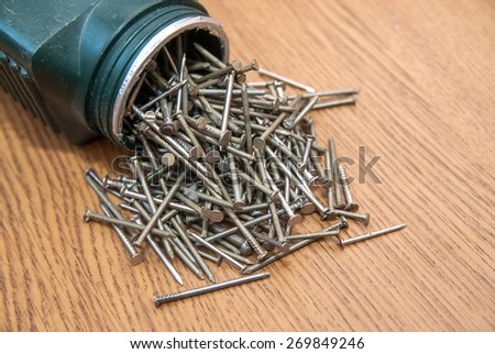 open box of old metal nails on wood background - stock photo