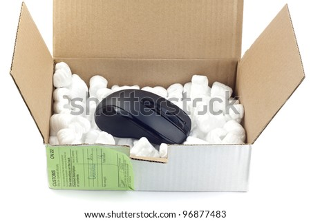 Open box with packing 'peanuts' and computer mouse isolated on white - stock photo