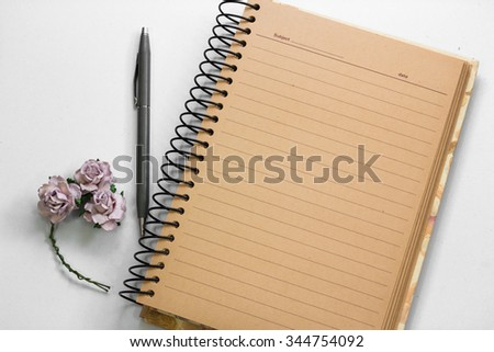 open brown paper note book with lined and gray pen on white back - stock photo
