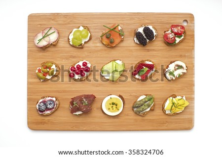 Open canape sandwiches and bite size crostinis on a wooden serving board. Party food crackers with toppings isolated on white. - stock photo