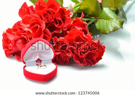 Open case with a ring on a white background next to a bouquet of roses - stock photo
