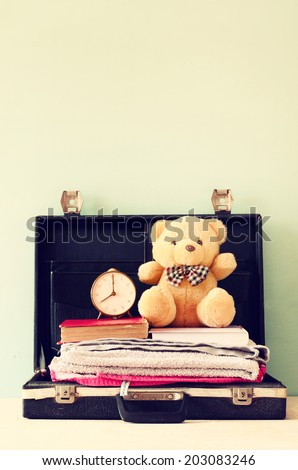 open case with books towel teddy bear and vintage clock. vacation concept. - stock photo