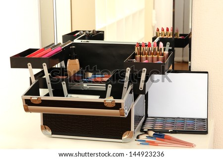 Open case with cosmetics on table near mirror - stock photo