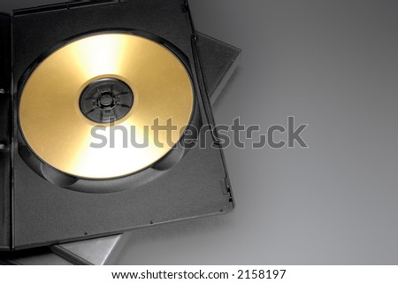 Open CD/DVD case with a golden disk - stock photo