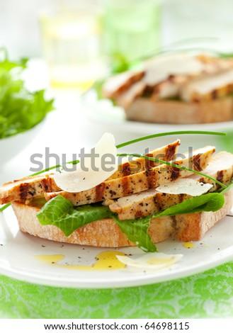 Open chicken Caesar sandwich on the white plate - stock photo