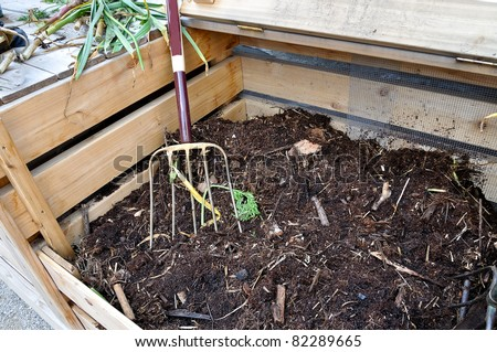 open compost bin with garden fork - stock photo