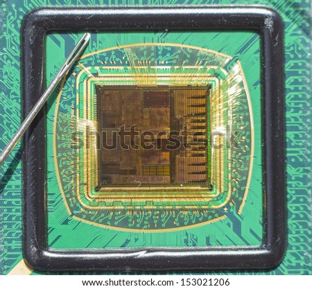 Open computer chip with gold wire connections compared to a needle - stock photo