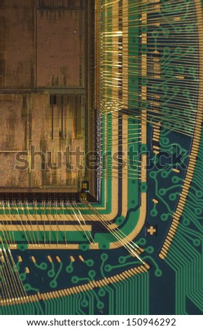 Open computer chip with gold wire connections compared to a niddle - stock photo