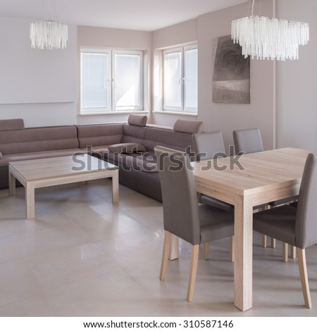Open-concept living room with comfortable sofa and place for dining - stock photo