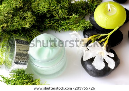 Open cream jar algae. Flowers, black stones and seaweed decoration. Top view - stock photo