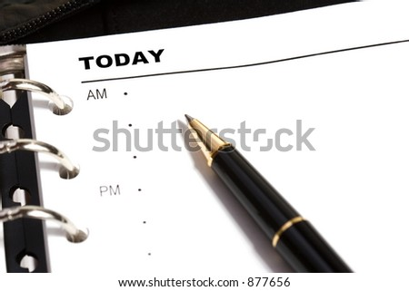 Open dayplanner with a ballpoint pen pointing to TODAY. - stock photo