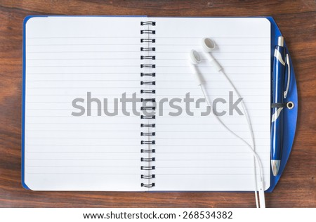 open diary, a pen and headphone on a wooden table. Study and journal concept - stock photo
