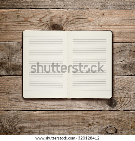 Open diary on wooden background - stock photo