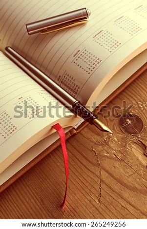 Open diary with one fountain pen in it, placed on a wood table. Vintage processing. - stock photo