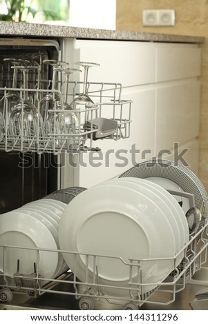 Open dishwasher with clean dishes, modern kitchen