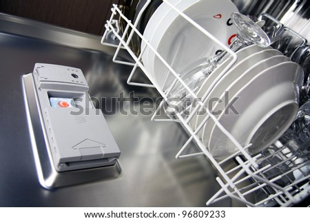 open dishwasher with clean plates in it, focus on dishwasher tabs - stock photo
