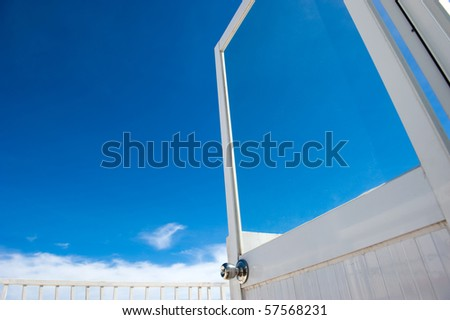 Open door against blue sky; opportunities, new beginning, success, freedom concepts - stock photo