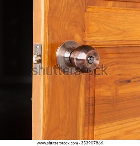 open door, door knob and keyhole on wooden door, close up image - stock photo