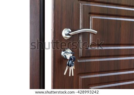 Open door handle. Door lock with keys. Brown wooden door closeup isolated. Modern interior design, door handle. New house concept. Real estate. - stock photo