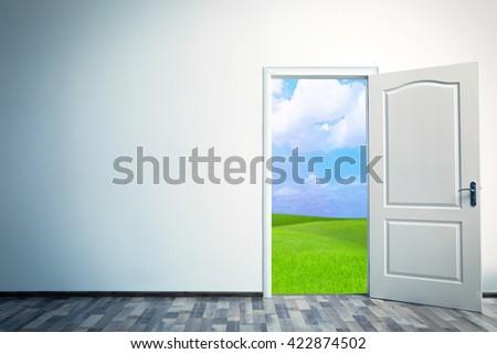 Open door leading to green field - stock photo