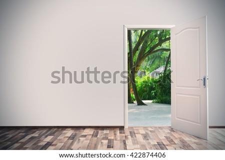 Open door leading to tropical garden - stock photo