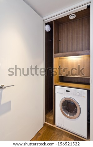 open door on a utility room with wooden shelving and washing machine  - stock photo