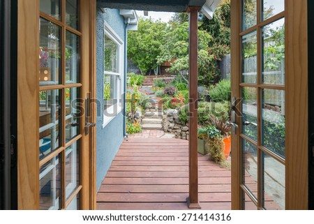 Open double french door doors with wooden deck leading to garden. - stock photo