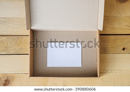 Open, empty box, front view,  on natural wooden table with white card inside.  - stock photo