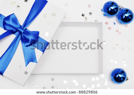 Open empty gift box with blue ribbon, confetti and balls - stock photo