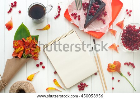 Open empty notebook with cup of coffee, red current cake slice, brushes and bouquet of flowers in the craft paper on the white wooden background, copy space. Top view. - stock photo