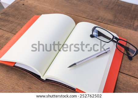 Open empty notebook with pen and glasses. - stock photo