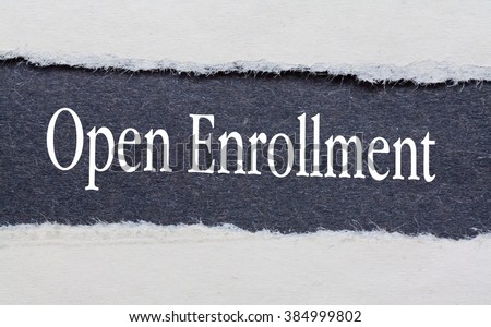 Open Enrollment words under torn black paper. - stock photo