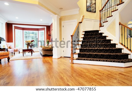 Open entryway with wood floor and staircase, with view of living room. Horizontal format. - stock photo