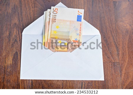 Open envelope with euro banknotes on table - stock photo