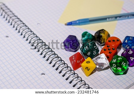 open exercise book with sticky card, pen and role playing dices - stock photo - stock photo