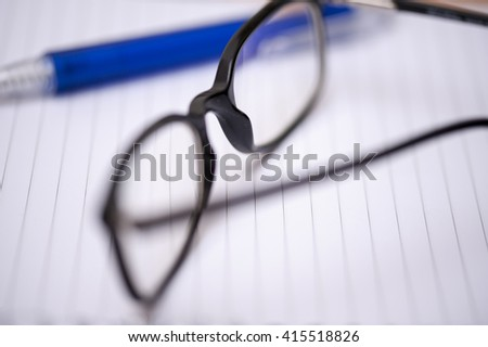 Open eyeglasses and a blue pen on a striped notebook. Selective focus.  - stock photo