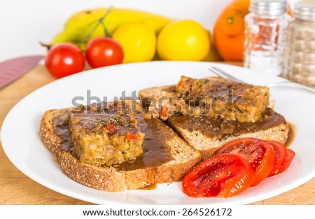 Open faced sandwich of meatloaf on whole grain bread smothered in brown gravy with sliced tomatoes.  Kitchen scene with knife, fruits and vegetables. - stock photo