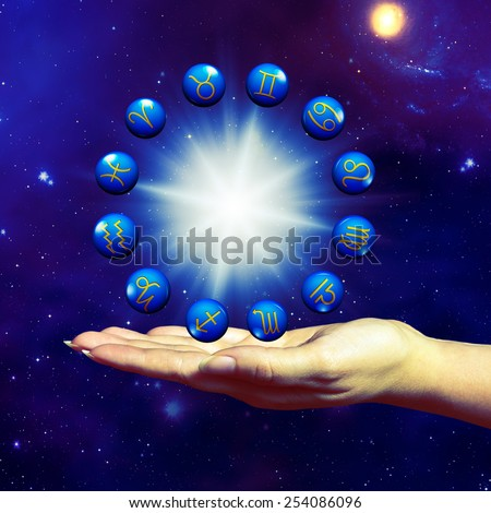 open female hand holding a zodiac wheel - Elements of this image furnished by NASA - stock photo