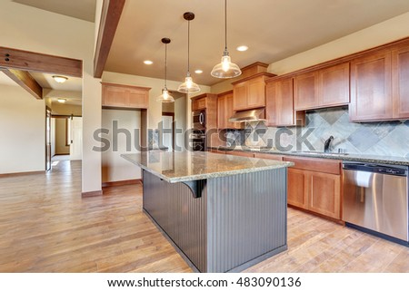 Open floor plan. Kitchen room interior with wooden cabinets, island and granite counter top. Northwest, USA