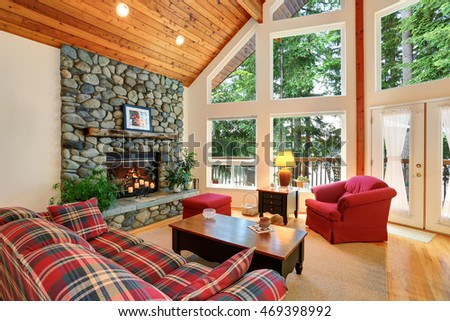 Open floor plan living room interior with rocks trim fireplace and big windows. Northwest, USA