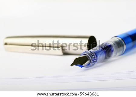 Open fountain pen resting on top of stacked white paper with copy space.