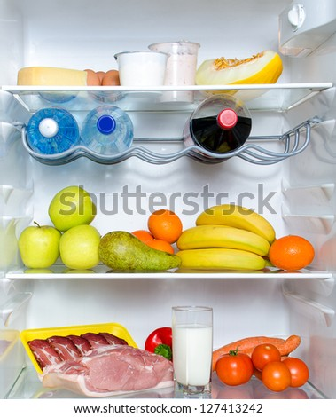 Open fridge full of fruits, vegetables and meat - stock photo