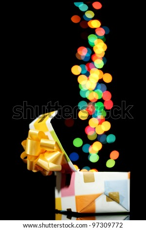 open gift box with bokeh background on black