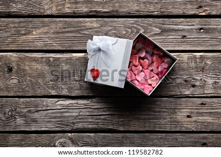 Open gift box with lots of cute little hearts inside. On old wood background. - stock photo
