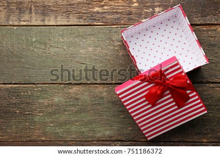 Open gift box with ribbon on wooden table